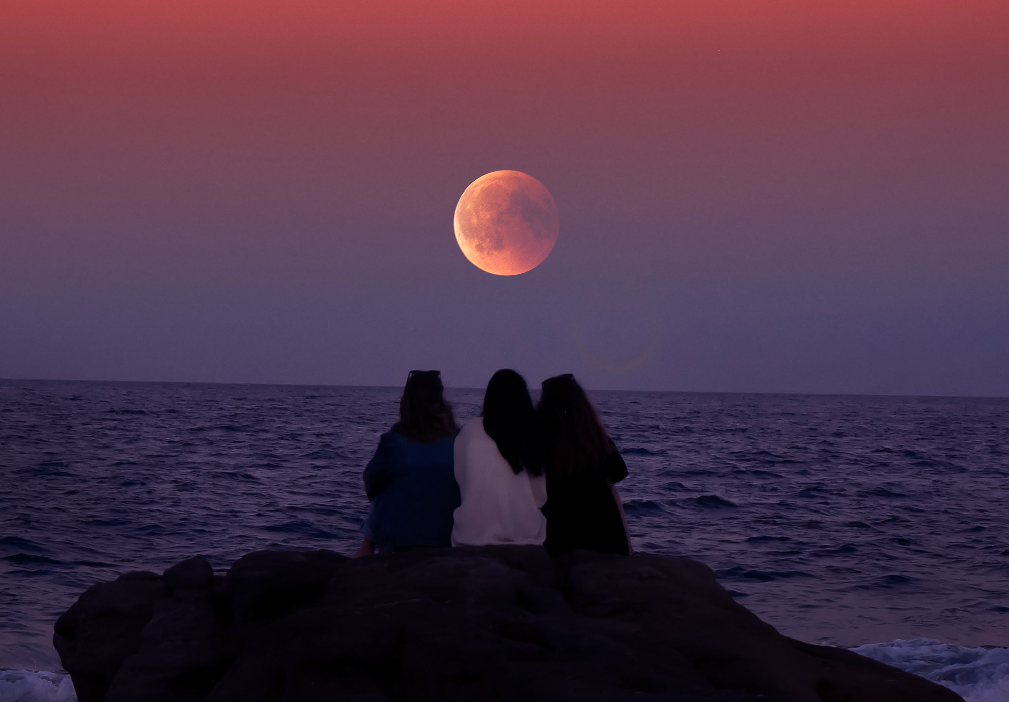 Three girls are sitting on a rock watching the sunset