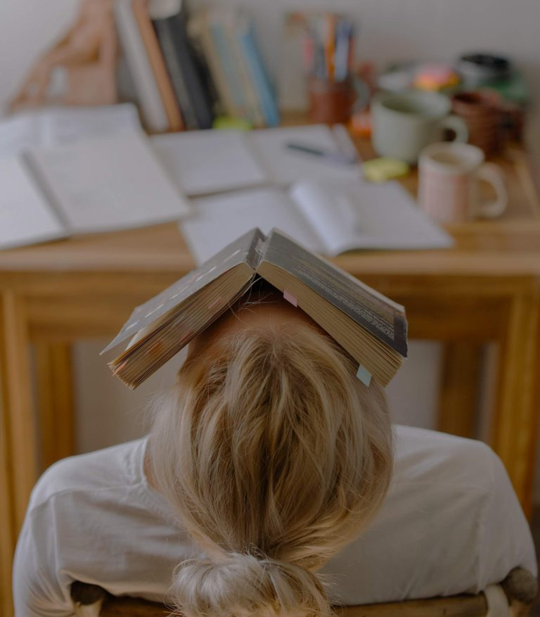 A stressed-out girl holds an open book to her face