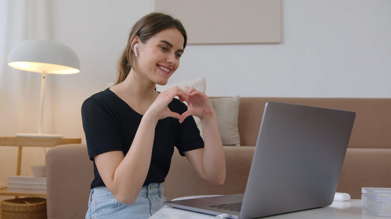 A girl makes a heart with her hands in front of a computer